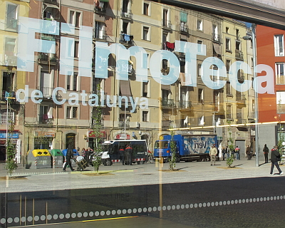 El Raval reflected in the window of the FilmoTeca flagship
